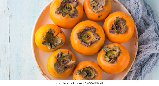 Ripe persimmons on turquoise background. Autumn winter fruit