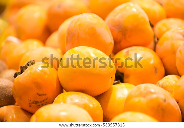 Ripe persimmons tiled on a market stall. Organic persimmon fruits in pile at local farmers market. persimmon background. Selective focus.