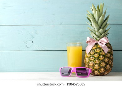 Ripe pineapple fruit with a pink bow, sunglasses and pineapple juice on a blue wooden background. place for text.