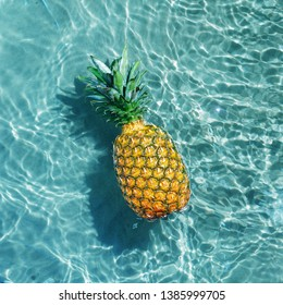 Ripe pineapple into water on sunny beach. Top view.