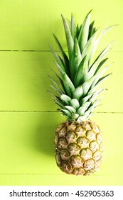 Ripe pineapple on a green wooden background