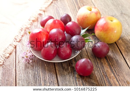 Ripe plums and apples lie on a wooden table. Side view.