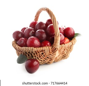 Ripe plums in basket on white background