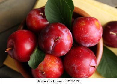 Ripe plums in bowl on wooden table with napkin, top view