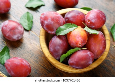 ripe plums on a wooden background, top view