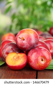 Ripe plums on wooden table on natural background