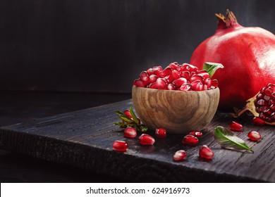 Ripe pomegranate fruit on a old  black wooden vintage background.