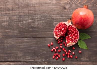 Ripe pomegranate fruit on wooden vintage background.