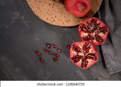 Ripe pomegranate fruit and pomegranate seeds on dark background, close-up. Healthy vegetarian antioxidant organic diet food