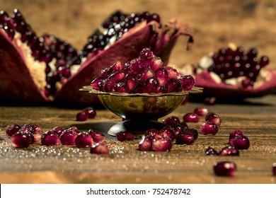 Ripe pomegranate fruit seeds on wooden vintage table