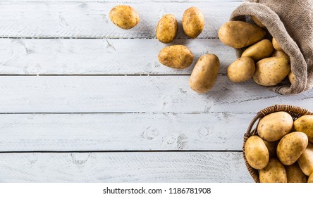 Ripe potatoes in burlap sack and wooden basket freely lying on wooden board.