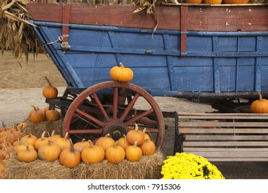 Ripe pumpkins around colorful farm wagon in autumn
