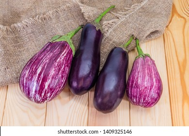 Ripe purple conventional eggplants and striped eggplants, so-called graffiti eggplant, on the wooden rustic table with burlap, top view