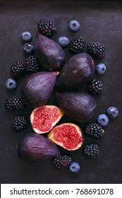 Ripe purple whole and cut figs, blackberries and blueberries on black background. Top view point. Dark moody image.