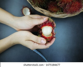 Ripe rambutan on hand ready to eat, Red rambutans, rambutans in your hand with knife.