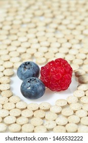 Ripe raspberries and blueberries are surrounded by pills on all sides. Concept: natural vitamins. Close up.