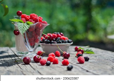 ripe raspberries and cherries on a wooden table in the garden