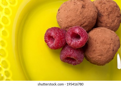 Ripe raspberry and chocolate truffles  closeup on yellow plate