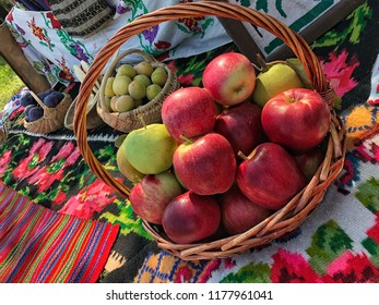 Ripe red apples and fruits in a basket at a park