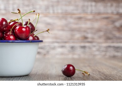 Ripe Red Cherries in a white enamelled tin dish
