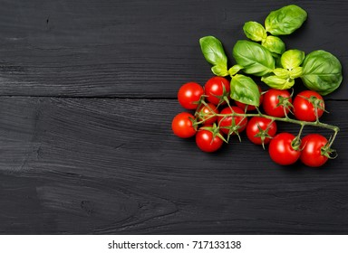 Ripe red cherry tomatoes with fresh basil leaves on black wooden table, top view with copy space