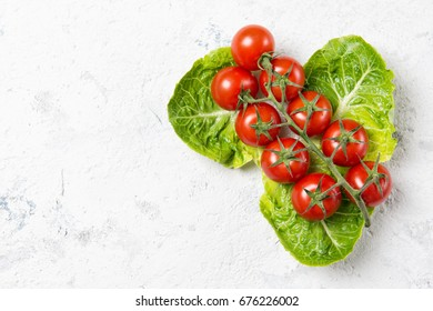 Ripe red cherry tomatoes on Romain Lettuce leaves, stone table, top view with copy space