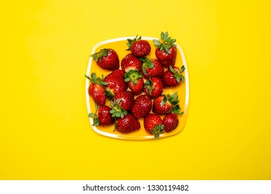 Ripe, red delicious strawberry lies in a square plate on a bright yellow background. Close-up.