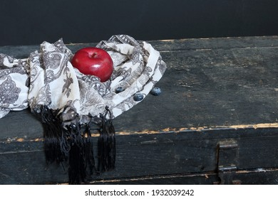 Ripe red macintosh apple positioned on black and white chiffon scarf placed on surface of old wooden vintage trunk