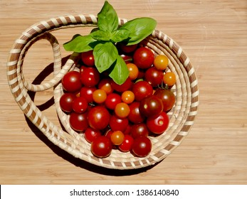 Ripe red and orange cherry tomatoes and basil in a Charleston sweetgrass braided basket on a wooden surface