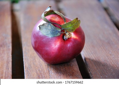 a ripe and red peach with some leaves isolated on a wooden table close up