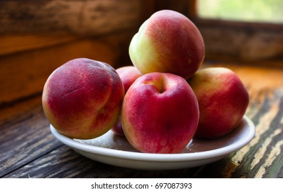 Ripe red peaches on a white plate on a wooden table