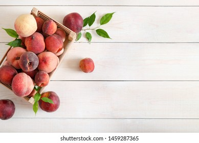 Ripe red peaches in a wooden box on a light background top view. Healthy fruit peach scattered on a wooden table