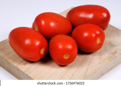 Ripe red Ppum tomatoes on a wooden chopping board.