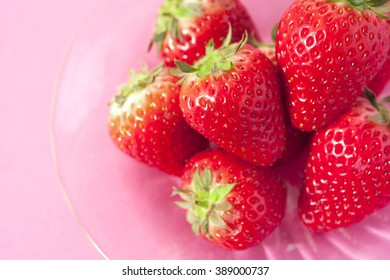 Ripe red strawberries on pink background