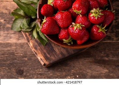 Ripe red strawberries on vintage wooden table