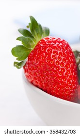 Ripe red strawberries in a white ceramic bowl on a white background. Closeup