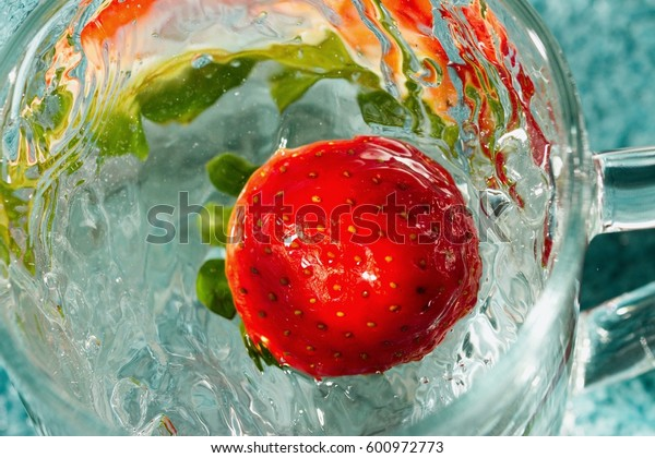 Ripe red strawberry falling into cup of water