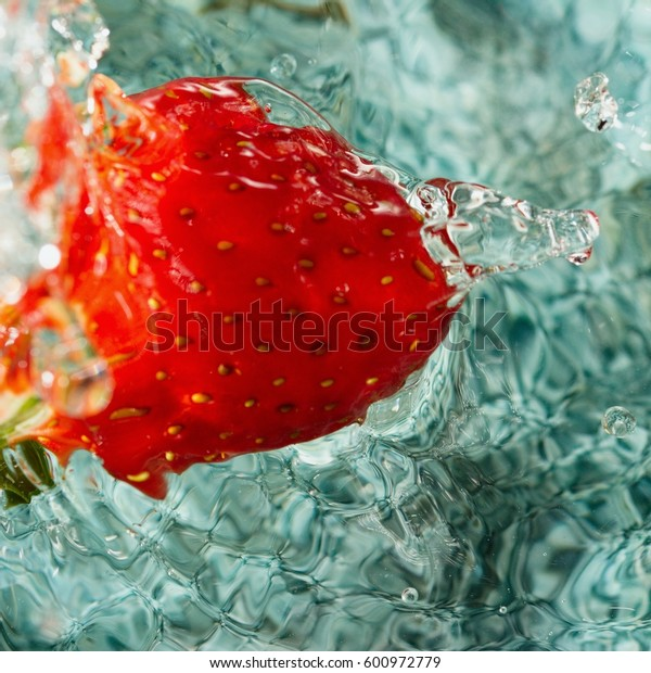 Ripe red strawberry falling into bowl of water