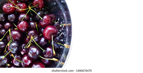 Ripe Red Sweet Cherries in metal colander with water drops isolated on white. Close-up of fresh red sweet cherries in metal colander on white surface. Fresh summer background.