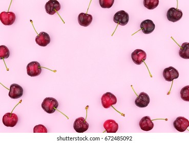 Ripe red sweet cherries on trendy pink background. Flat lay style. Colorful diet and healthy food concept.