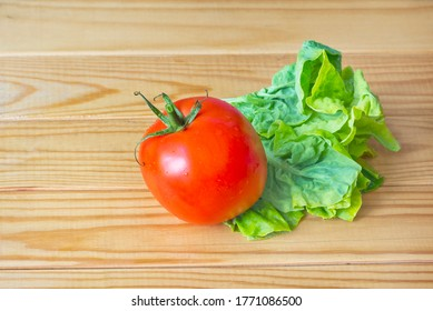 Ripe red tomato and green salad on wooden table
