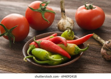 Ripe red tomatoes, hot chili peppers, garlic on a wooden table