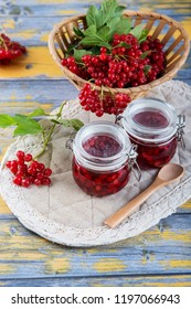 Ripe red viburnum berries and a small glass jar with freshly prepared jam on a light wooden table. Autumn harvest. The source of natural vitamins.