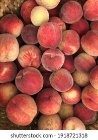 Ripe ruddy peaches with a red side, recently picked from the garden.