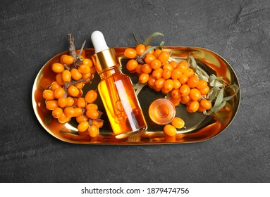 Ripe sea buckthorn and bottles of essential oil on black table, top view