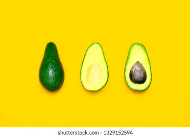 Ripe sliced avocado on bright yellow background top view. Creative food composition Flat lay. Pop art design, tropical summer abstract background with avocado. Green avocadoes pattern, diet concept