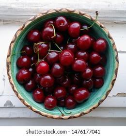 ripe sour cherries in ceramic bowl