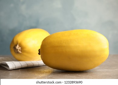 Ripe spaghetti squashes on gray table against color background