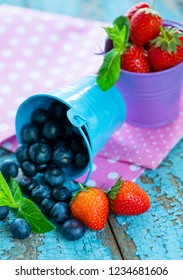 Ripe strawberries and blueberries in blue buckets. Healthy eating concept