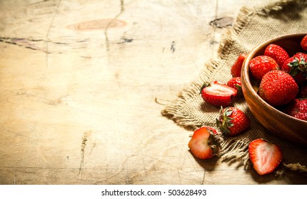 Ripe strawberries in bowl on a sack. On wooden background.